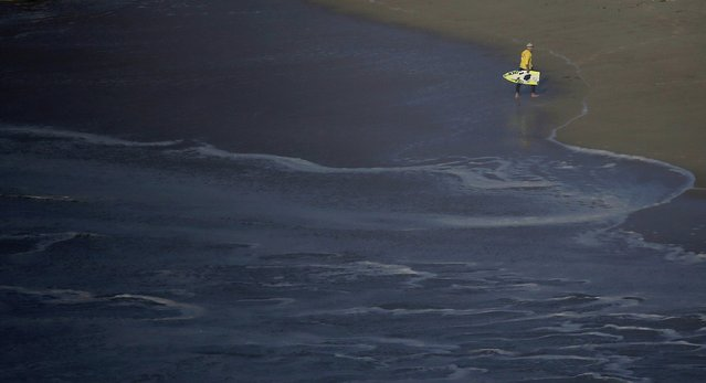A man picks up a broken surf board during a tow-in surfing session at Praia do Norte, in Nazare December 11, 2014. (Photo by Rafael Marchante/Reuters)