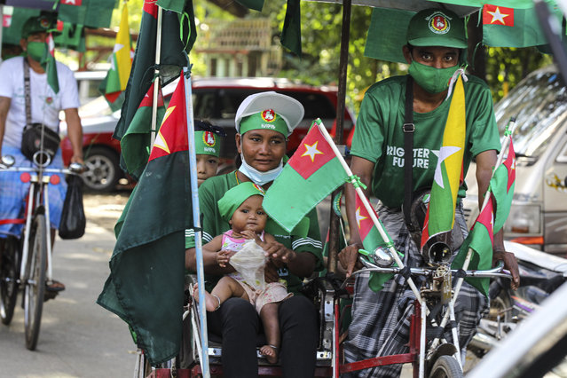 A supporter of the military-backed Union Solidarity and Development Party (USDP) holds a toddler while onboard a trishaw during an election campaign motorcade in Yangon, Myanmar, on Thursday, November 5, 2020. Myanmar's citizens go to the polls Sunday, Nov. 8, in an effort to sustain the fledgling democracy they helped install just five years ago. (Photo by Thein Zaw/AP Photo)