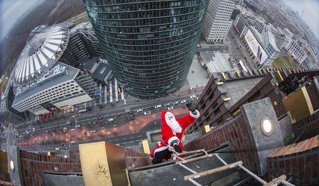 A man dressed as a Santa Claus waves as he climbs at the front of the Kollhoff Tower at Potsdamer Platz square in Berlin December 14, 2014. (Photo by Hannibal Hanschke/Reuters)