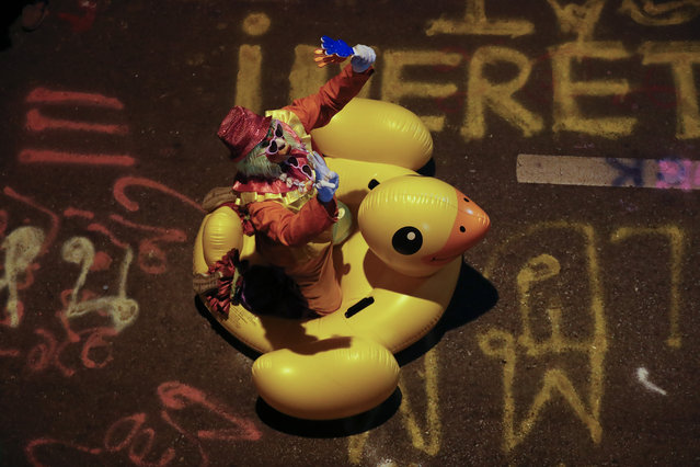 A clown carries a large inflatable duck at a pro-democracy rally in Bangkok, Thailand, Wednesday, November 18, 2020. (Photo by Sakchai Lalit/AP Photo)