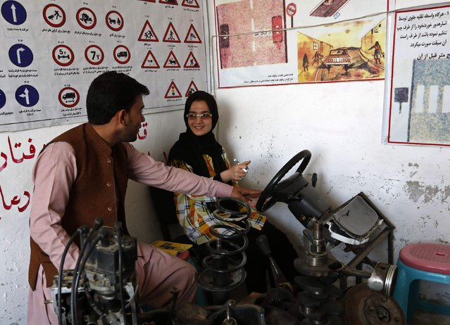 Tahmina, (R) talks to her instructor during a practical lesson at a driving school in Kabul September 4, 2014. (Photo by Mohammad Ismail/Reuters)