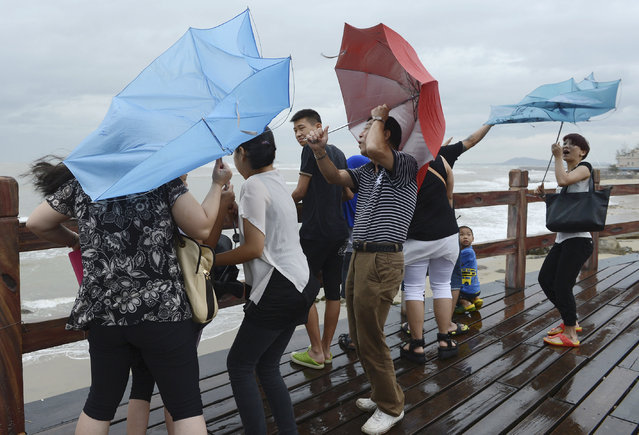 People hold onto their umbrellas as they encounter strong winds near the coast as Typhoon Utor hits Yangjiang, Guangdong province, China, August 14, 2013. (Photo by Reuters/Stringer)
