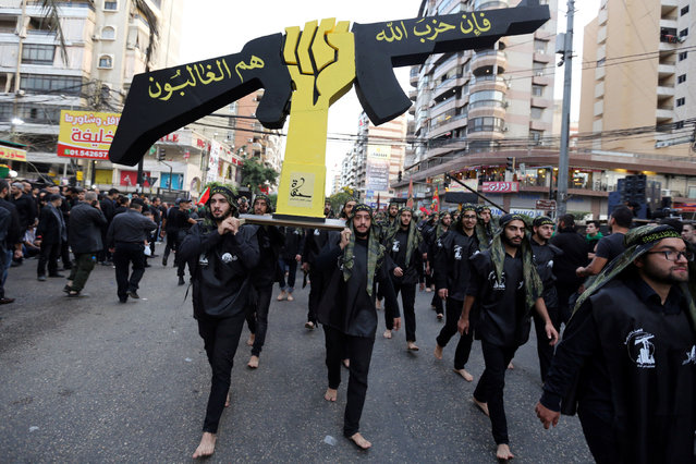 Lebanese Hezbollah supporters carry a replica of Hezbollah emblem during a religious procession to mark Ashura in Beirut's southern suburbs, Lebanon October 12, 2016. (Photo by Aziz Taher/Reuters)