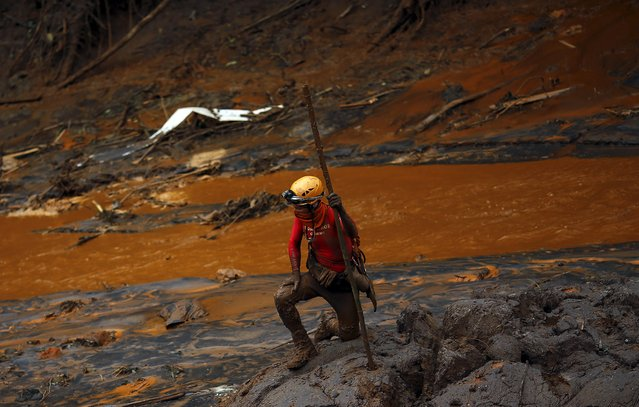 A rescue worker searches for victims at Bento Rodrigues district that was covered with mud after a dam owned by Vale SA and BHP Billiton Ltd burst, in Mariana, Brazil, November 8, 2015. (Photo by Ricardo Moraes/Reuters)