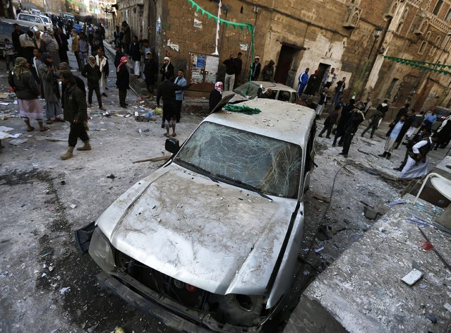 People gather at the site of a bomb explosion in Sanaa December 23, 2014. Five bombs exploded on Tuesday in Sanaa's old quarter, where many supporters of the Shi'ite Muslim Houthi group live, killing at least one person and wounding another, a Yemeni security official said. (Photo by Khaled Abdullah/Reuters)