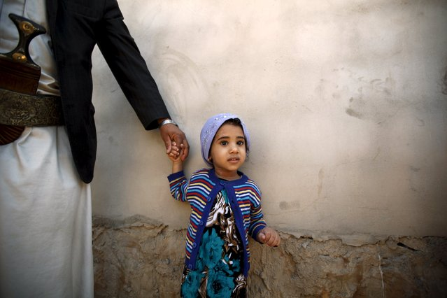 A girl holds her father's hand after she received polio vaccine drops during a house-to-house vaccination campaign in Yemen's capital Sanaa, November 10, 2015. (Photo by Khaled Abdullah/Reuters)