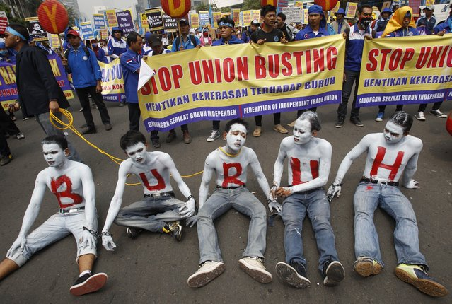 """Indonesian workers with their faces and bodies painted in white and an Indonesian word """"Buruh"""" that means """"Workers"""" in red take part in a rally commemorating May Day in Jakarta, Indonesia, Wednesday, May 1, 2013. (Photo by Achmad Ibrahim/AP Photo)"""