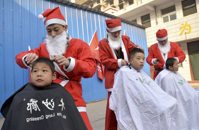 Volunteers in Santa Claus costumes give free hair cuts to children at a welfare house to celebrate the upcoming Christmas festivities in Handan, Hebei province December 24, 2014. (Photo by Reuters/Stringer)