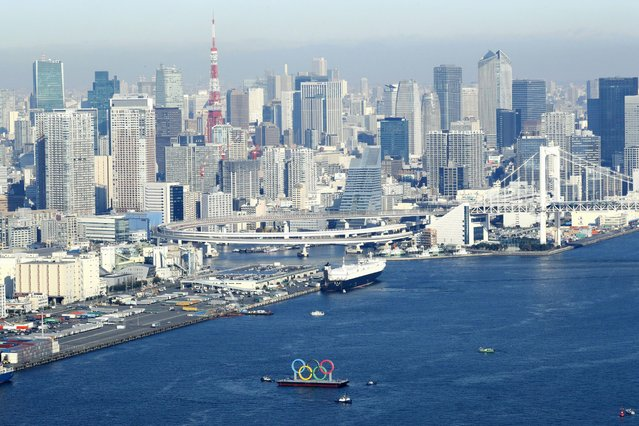 Photo taken December 1, 2020, from a Kyodo News helicopter shows the Olympic rings being transported ahead of their reinstallation in Tokyo Bay after undergoing a safety inspection and maintenance. The rings were temporarily removed in August following the Tokyo Summer Games' postponement until 2021 due to the coronavirus pandemic. (Photo by Kyodo News via Getty Images)