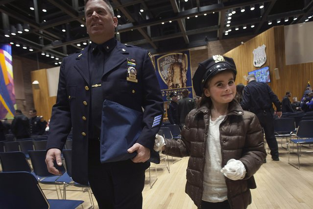Karen Tanner, daughter of Nick Tanner, tries on his hat and gloves after her father was promoted to the rank of Detective Specialist during a New York Police Department Promotion Ceremony at Police Headquarters in the Manhattan borough of New York, December 19, 2014. (Photo by Carlo Allegri/Reuters)