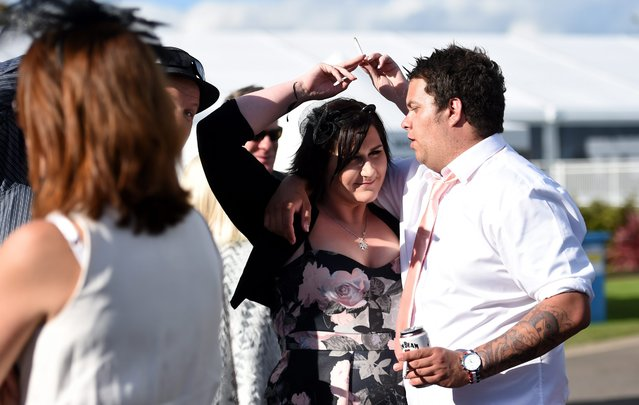 Race goers pass a cigarette between each other after the Geelong Cup on Geelong Cup day at Geelong Racecourse in Melbourne, Australia, 19 October 2016. (Photo by Tracey Nearmy/EPA)