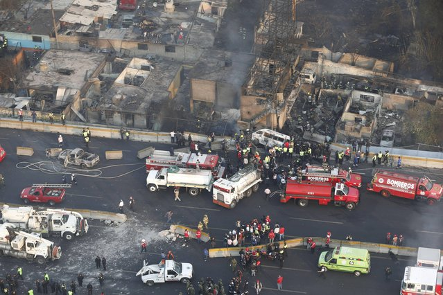 Aerial view shows first responders working next to destroyed homes and vehicles after a gas tanker truck exploded on a highway in the Mexico City suburb of Ecatepec early Tuesday, May 7, 2013. The blast killed and injured dozens, according to the Citizen Safety Department of Mexico State. Officials did not rule out the possibility the death toll could rise as emergency workers continued sifting through the charred remains of vehicles and homes built near the highway on the northern edge of the metropolis. (Photo by AP Photo)