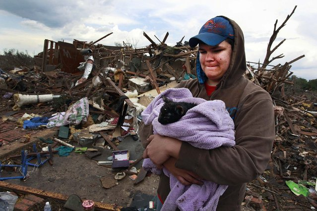 Austin Brock holdshis  cat Tutti, shortly after the animal was retrieved from the rubble of Brock's home in Moore on Tuesday. (Photo by Brennan Linsley/Associated Press)