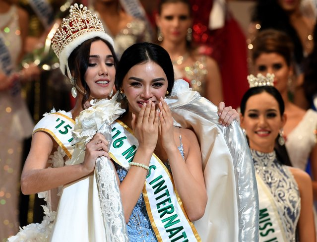 Newly elected 2016 Miss International Kylie Verzosa from Philippines (C) receives her gown from 2015 Miss International Edymar Martinez from Venezuela (L) during the Miss International beauty pageant final in Tokyo on October 27, 2016. (Photo by Toshifumi Kitamura/AFP Photo)