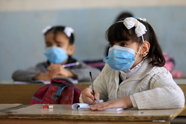 Students wear masks as a measure taken against coronavirus (Covid-19) pandemic attend the lesson at a school in Baghdad, Iraq on December 6, 2020. (Photo by Murtadha Al-Sudani/Anadolu Agency via Getty Images)