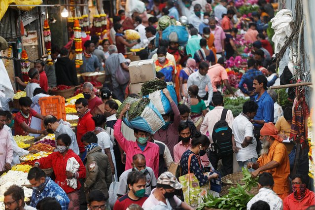 People are seen at a crowded market amidst the spread of the coronavirus disease in Mumbai, India, December 30, 2020. (Photo by Francis Mascarenhas/Reuters)