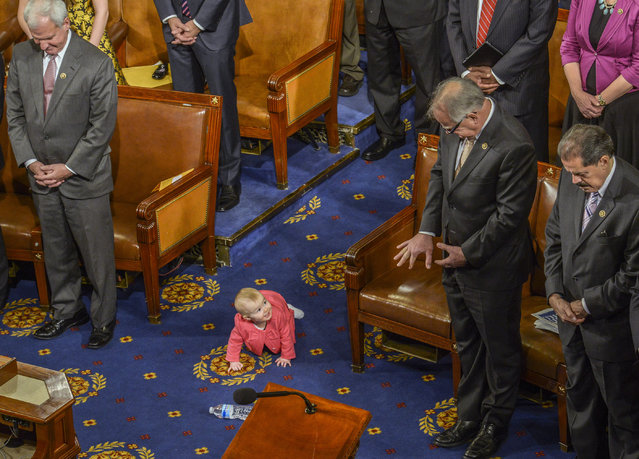 Caroline Yoder, center, the baby daughter of Rep. Kevin Yoder (R-KS) makes a friend across the aisle as representatives stand for the prayer on opening day of the 114th Congress, on January, 06, 2015 in Washington, DC. (Photo by Bill O'Leary/The Washington Post)