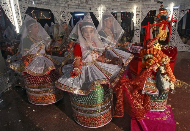 Artists wearing traditional dresses perform during the Hindu festival of Maha Raas in Agartala, India, November 26, 2015. The annual Hindu festival is celebrated on the full moon night of 'Karthik Purnima' in the holy month of 'Karthik' to mark Lord Krishna's love for Radha, his consort. (Photo by Jayanta Dey/Reuters)