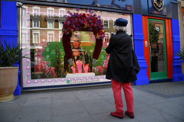 A passer-by views a floral display and design outside of a shop front which is participating in the Chelsea In Bloom festival in London, Britain on May 22, 2018. (Photo by Toby Melville/Reuters)