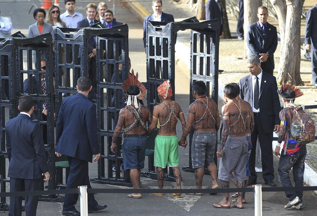 Munduruku Indians pass through a metal detector as they arrive for a meeting with the Minister of the General Secretariat of the Presidency, Gilberto Carvalho, at the Planalto Palace in Brasilia, June 4, 2013. (Photo by Ueslei Marcelino/Reuters)