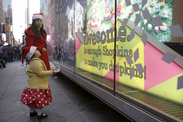 "A girl peers through the window at Toys ""R"" Us Times Square store during the early opening of the Black Friday sales in the Manhattan borough of New York, November 26, 2015. (Photo by Andrew Kelly/Reuters)"