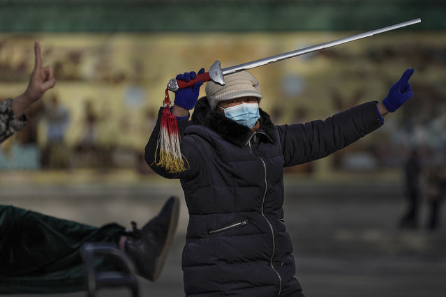 A woman wearing a face mask to help curb the spread of the coronavirus performs a morning exercise with a sword at a public park in Beijing, Tuesday, January 12, 2021. Lockdowns have been expanded and a major political conference postponed in a province next to Beijing that is the scene of China's most serious recent COVID-19 outbreak. (Photo by Andy Wong/AP Photo)