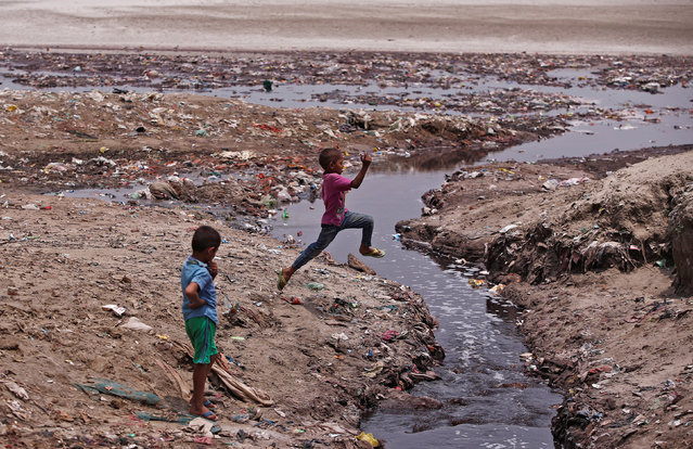A boy jumps over a drain flowing with waste water from the leather tanneries into the river Ganges in Kanpur, India, May 3, 2018. Picture taken May 3, 2018. (Photo by Adnan Abidi/Reuters)