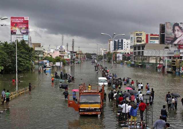 People stand on a flooded road in Chennai, India, December 2, 2015. (Photo by Reuters/Stringer)