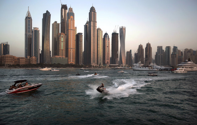 In this Friday, April 10, 2015 photo, people use recreational vehicles opposite the Marina district of Dubai, United Arab Emirates. (Photo by Kamran Jebreili/AP Photo)