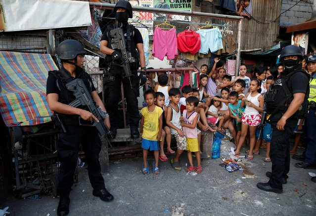 Members of Philippine National Police SWAT team stand guard near the residents during an anti-drugs operation, in Pasig, Metro Manila in the Philippines, November 9, 2016. (Photo by Erik De Castro/Reuters)