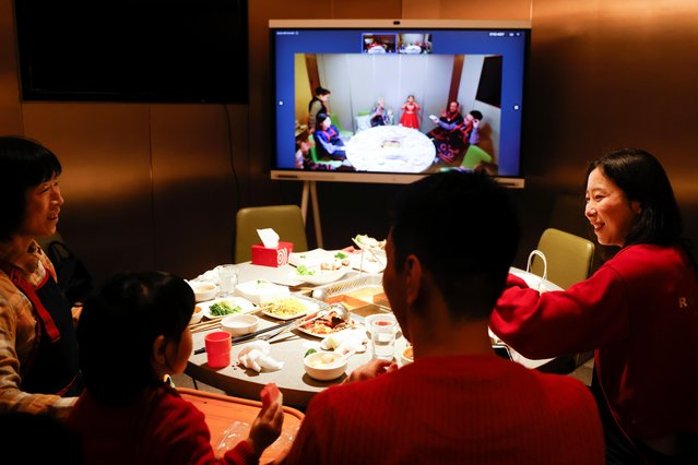 Liu Yuting and her family enjoy Lunar New Year dinner at a Haidilao hotpot restaurant with relatives in Jilin province via video link after they decided not to travel to their hometown following authorities' advice after a coronavirus outbreak in Beijing, China on February 11, 2021. (Photo by Carlos Garcia Rawlins/Reuters)