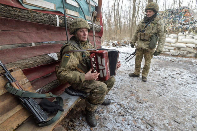 A Ukrainian service member plays the musical instrument at fighting positions on the contact line with Russian-backed separatist rebels near the town of Avdiivka in Donetsk Region, Ukraine on February 13, 2021. (Photo by Oleksandr Klymenko/Reuters)