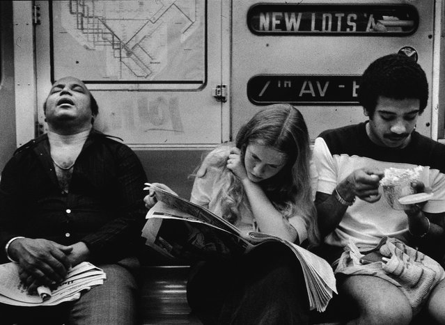 A view of three people sitting on the Number 2 line (7 Avenue Express) IRT subway, New York, in the 1970s. One man sleeps, a young woman reads a newspaper, and a young man eats. (Photo by Tony Vaccaro/Getty Images)