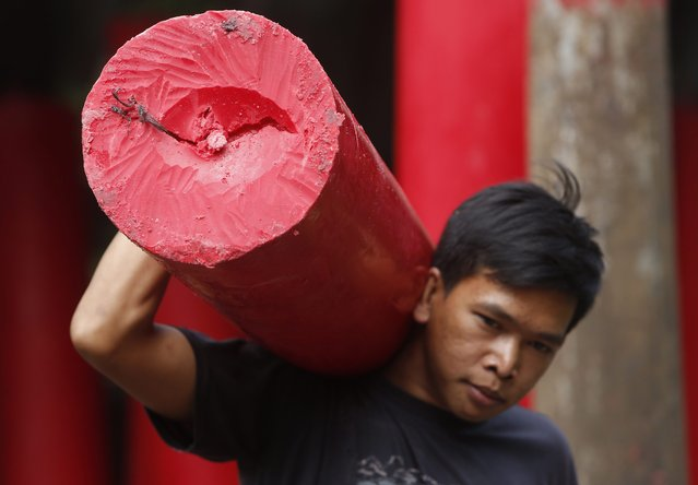 An Indonesian worker carries a giant candle at a traditional Chinese candle maker for the upcoming Lunar New Year in Bogor, Indonesia, 27 January  2015. The Chinese Lunar New Year, known here as Imlek, is only three weeks away. The whole city is getting decked out to celebrate the event on 19 February 2015. (Photo by Adi Weda/EPA)