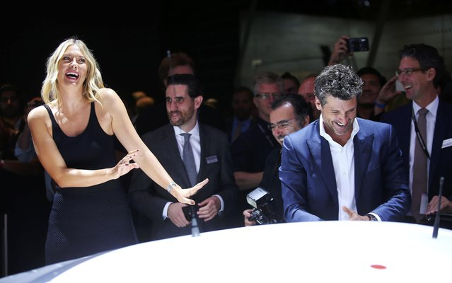 Tennis star Maria Sharapova (L) reacts as actor Patrick Dempsey tries to convince her to get into a Porsche 911 RSR race car at the 2016 Los Angeles Auto Show in Los Angeles, California, U.S November 16, 2016. (Photo by Mike Blake/Reuters)