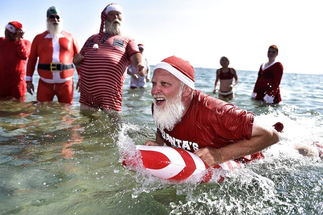 Actors dressed as Santa Claus take a refreshing bath at Bellevue Beach north of Copenhagen, Denmark, on July 24, 2018, as they take part in the World Santa Congress, an annual two-day event held every summer in Copenhagen. (Photo by Mads Claus Rasmussen/AFP Photo/Ritzau Scanpix)