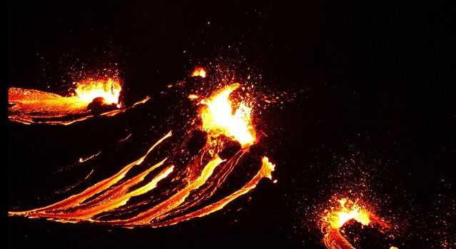 In this still image captured from a hand out video, filmed by the Icelandic Coast Guard, lava flows from the erupting Fagradalsfjall volcano some 50 km west of the Icelandic capital Reykjavik, on March 19, 2021. A volcano erupted in Iceland on Friday some 40 kilometres (25 miles) from the capital Reykjavik, the Icelandic Meteorological Office said, as a red cloud lit up the night sky and a no-fly zone was established in the area. (Photo by Icelandic Coast Guard/AFP Photo)