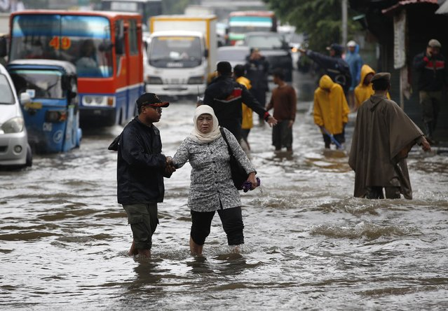 A woman is helped across a flooded intersection after continues heavy seasonal rains have flooded parts of Jakarta February 10, 2015. (Photo by Darren Whiteside/Reuters)