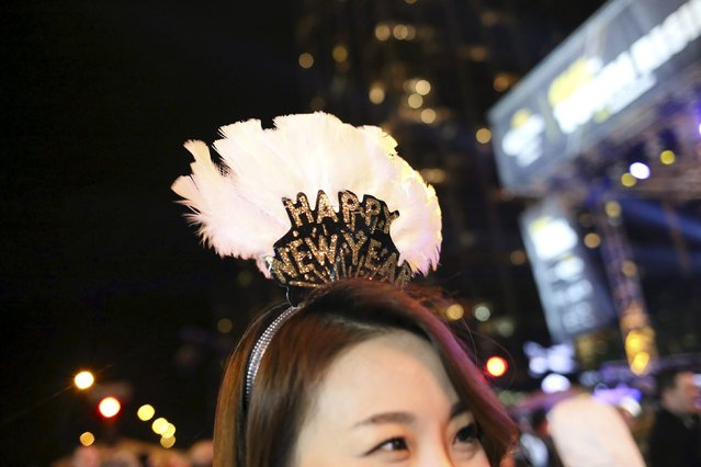 Kate Kim, 30, from Chicago, wears a holiday tiara while celebrating before the New Year at Chi-Town Rising in Chicago, Illinois, December 31, 2015. The event is set to feature a 70-foot-star that will rise to the top of the Hyatt Regency Chicago at midnight. (Photo by Alex Wroblewski/Reuters)