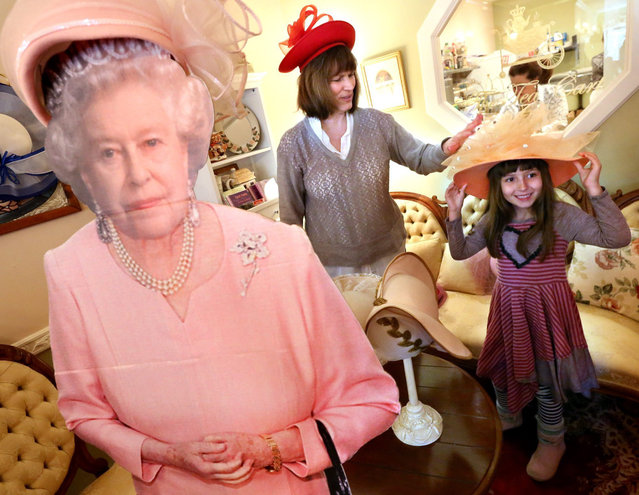 Lucy Chesley, 6, of Los Angeles, tries on hats with the help of her grandmother, Judith O'Hara, of Harper's Ferry, W.Va., behind a cardboard image of Queen Elizabeth II during a Downton Abbey Tea Party at The Tea Cart in Berryville, Va., Saturday, January 2, 2016. (Photo by Jeff Taylor/The Winchester Star via AP Photo)