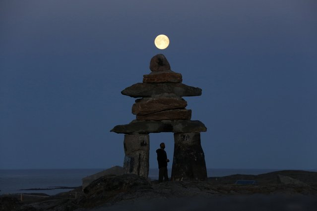 A man looks at a giant inukshuk as the moon rises above it in Rankin Inlet, Nunavut, Canada, on August 21, 2013. The inukshuk is a stone landmark or cairn used by the Inuit people in the arctic. (Photo by Chris Wattie/Reuters)