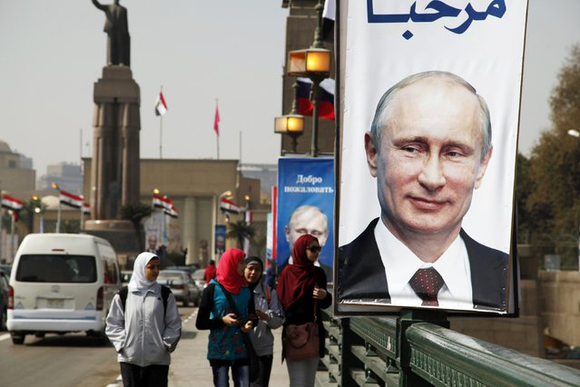 Girls walk past a banner with a picture of Russian President Vladimir Putin along a bridge, in central Cairo February 9, 2015. Putin is due to arrive on Monday on his first visit to Egypt in ten years. (Photo by Asmaa Waguih/Reuters)