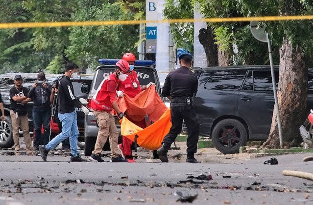 Police officer and rescue workers carry a body bag containing what is believed to be human remains outside a church where an explosion went off in Makassar, South Sulawesi, Indonesia, Sunday, March 28, 2021. A suicide bomber blew himself up outside a packed Roman Catholic cathedral on Indonesia's Sulawesi island during a Palm Sunday Mass, wounding a number of people, police said. (Photo by Masyudi S. Firmansyah/AP Photo)