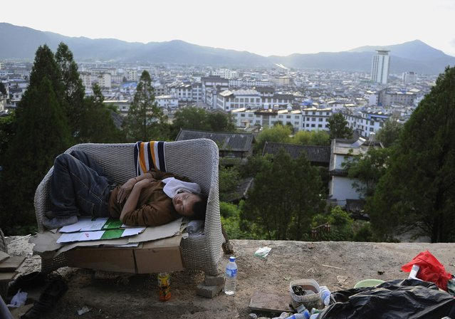 A garbage collector sleeps on a couch on the edge of a hilly road in Lijiang, Yunnan province, August 2, 2013. (Photo by Reuters/Stringer)