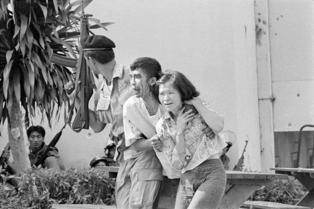 In this October 6, 1976, file photo, a leftist student, center, wounded and captured by police is helped to an ambulance during the student massacre at the Thammasat University campus in Bangkok, Thailand. This year's anti-government protests are seeking new elections, a more democratic constitution and an end to intimidation of political activists. Their speeches have repeatedly highlighted the 1976 tragedy, piquing the interest of the current generation in what their forebears faced. (Photo by Neal Ulevich/AP Photo/File)