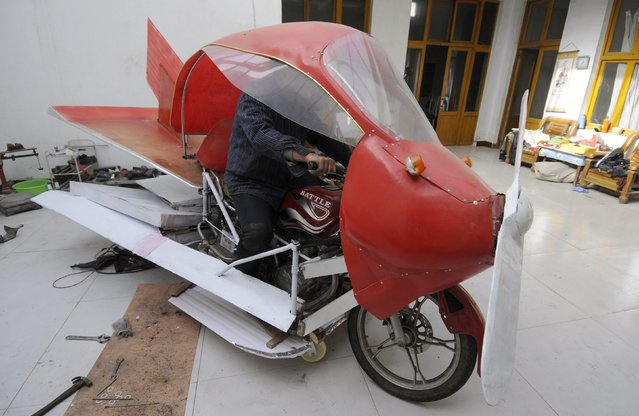 Zhang Xuelin sits inside his self-made aircraft at his home before its test flight in Jinan, Shandong province, November 28, 2012. Zhang, a farmer who dropped out of primary school in his early years, spent around 2,000 yuan ($321) to build a plane around a motorcycle, using wood and plastic boards. The plane, which took 11 months to build, failed in its test flight. (Photo by Reuters/China Daily)