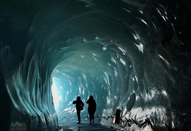 Visitors walk through a man-made ice cave inside the Mer de Glace valley glacier, one of the largest in the Alps despite large substantial melting in recent decades, in Chamonix, France on September 4, 2018. (Photo by Toby Melville/Reuters)