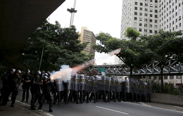 Riot police fire tear gas at demonstrators during a protest against fare hikes for city buses in Sao Paulo, Brazil, January 8, 2016. Brazilian riot police on Friday fired tear gas and stun grenades to disperse a violent protest against a rise in public transport fares in the country's largest city, Sao Paulo. (Photo by Nacho Doce/Reuters)