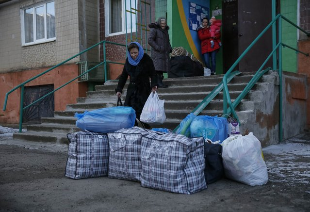 Local residents gather their personal belongings as they leave a residential sector affected by shelling in Kramatorsk, eastern Ukraine February 11, 2015. (Photo by Gleb Garanich/Reuters)