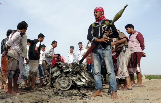People gather at the site of a car bomb attack in Yemen's southern port city of Aden January 5, 2016. Three senior southern Yemeni officials survived a suicide car bomb attack on their convoy in Aden and a subsequent gun battle that killed three of their guards on Tuesday, a government spokesman and security sources said. (Photo by Nasser Awad/Reuters)